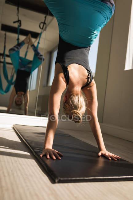 Женщина упражняется на раскачивающемся гамаке в фитнес-студии — стоковое фото