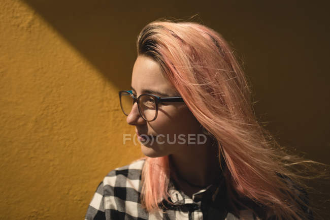 Young woman posing for camera against a wall — Stock Photo