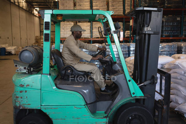 Mid section of male worker driving forklift in warehouse — Stock Photo