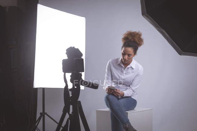Фотограф-женщина с мобильного телефона в фотостудии — стоковое фото