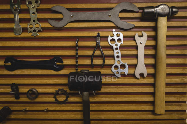 Various work equipment hanging on wooden wall — Stock Photo