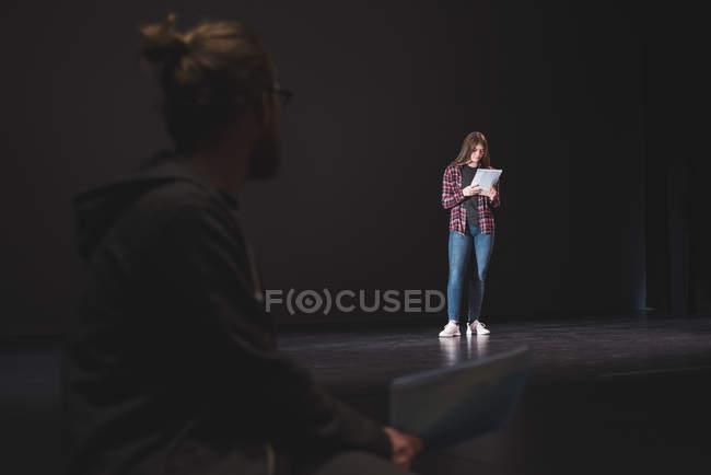 Actrice lecture script tandis que l'acteur masculin regarder spectacle sur scène au théâtre — Photo de stock