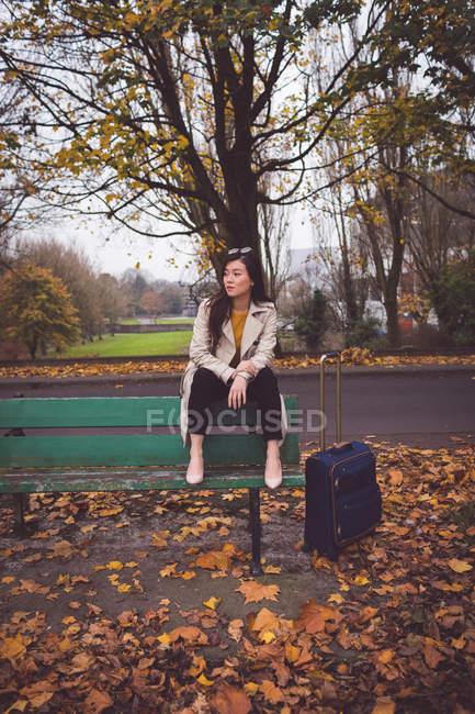 Nachdenkliche Geschäftsfrau sitzt im Herbst auf Bank — Stockfoto