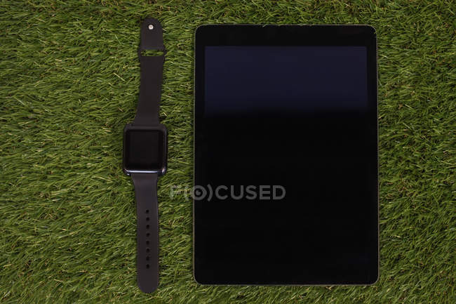 Smartwatch and digital tablet on artificial grass — Stock Photo