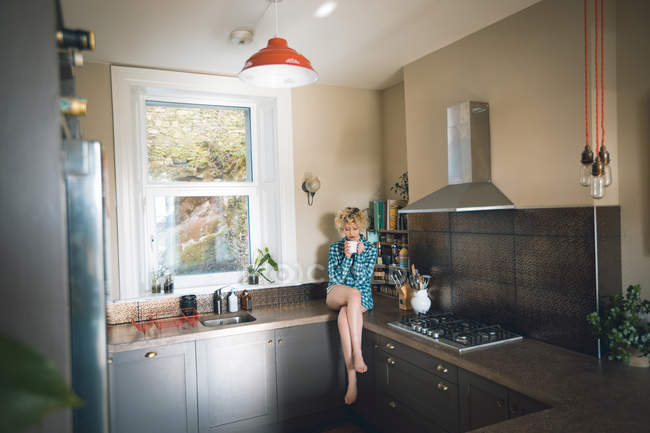 Young woman having in kitchen at home — Stock Photo