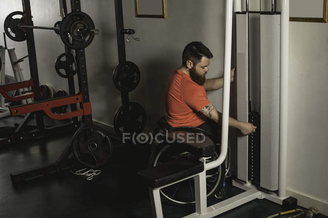 Handicapped man on wheelchair increasing weight of pulldown exercise in gym — Stock Photo