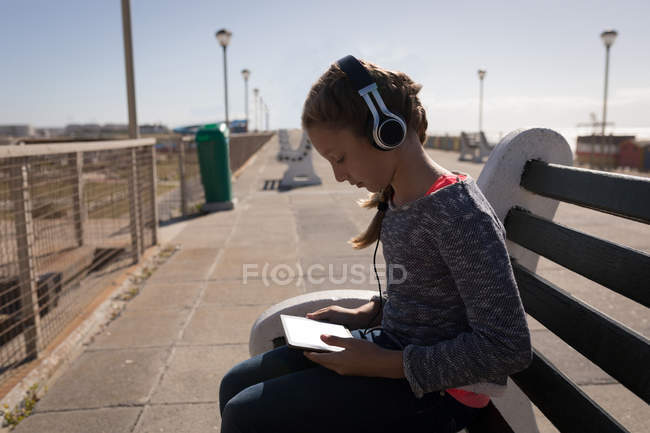Girl using digital tablet at pavement on a sunny day — Stock Photo