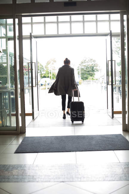 Rear view of woman with trolley bag leaving hotel — Stock Photo