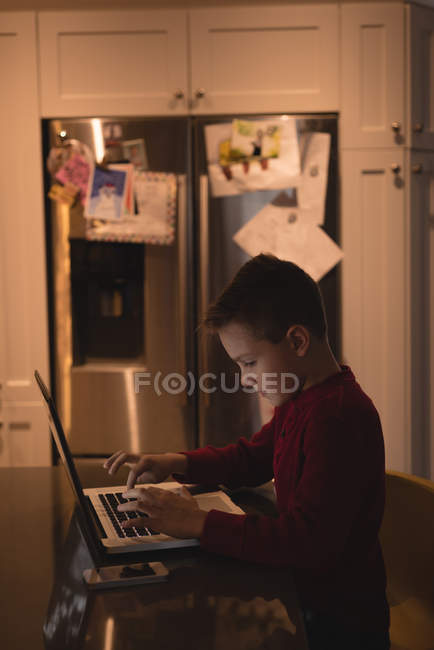 Side view of boy using laptop at home — Stock Photo