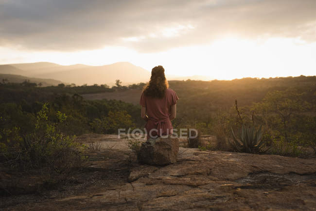 Rear view of woman sitting on rock and looking at nature — Stock Photo
