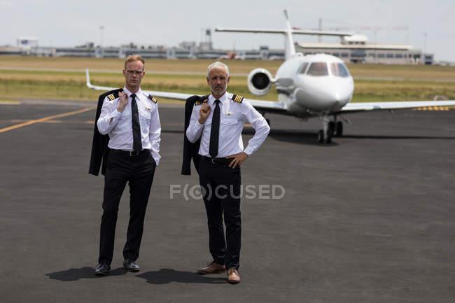 Два мужчины пилотов, стоя на взлетно-посадочной полосы — стоковое фото