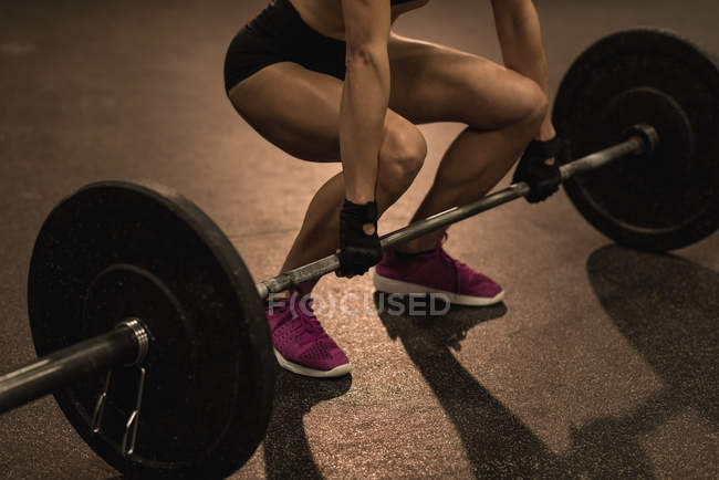 Low section of fit woman exercising with barbell in the studio — Stock Photo