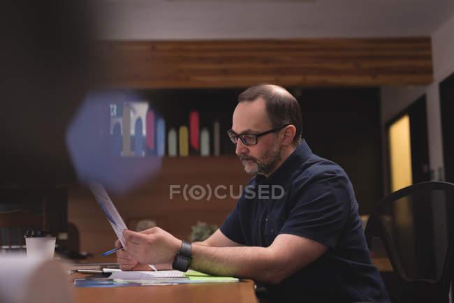 Executivo masculino, olhando para o gráfico de documento no escritório — Fotografia de Stock