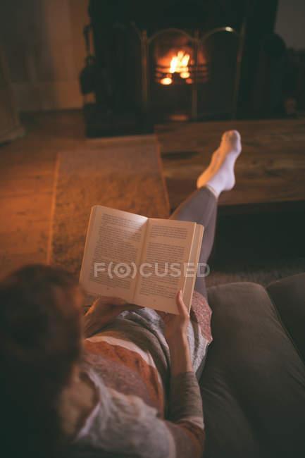 Donna che legge un libro in salotto a casa — Foto stock
