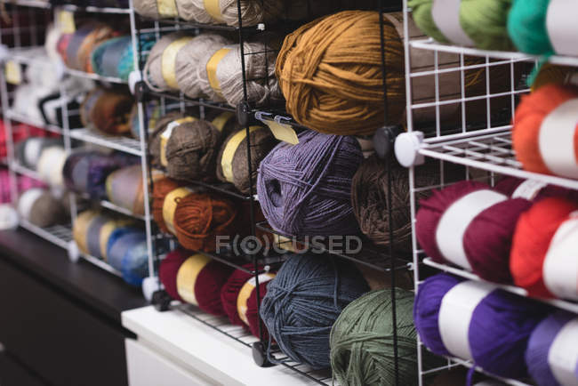 Multicolored ball of yarn kept on shelf in tailor shop — Stock Photo