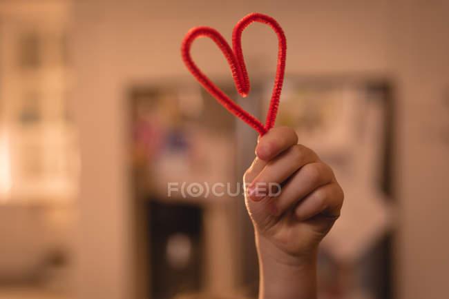 Close-up da menina segurando a decoração de forma de coração em casa — Fotografia de Stock