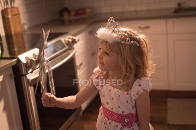 Дівчина у вінку з володіти чарівною паличкою вдома — стокове фото