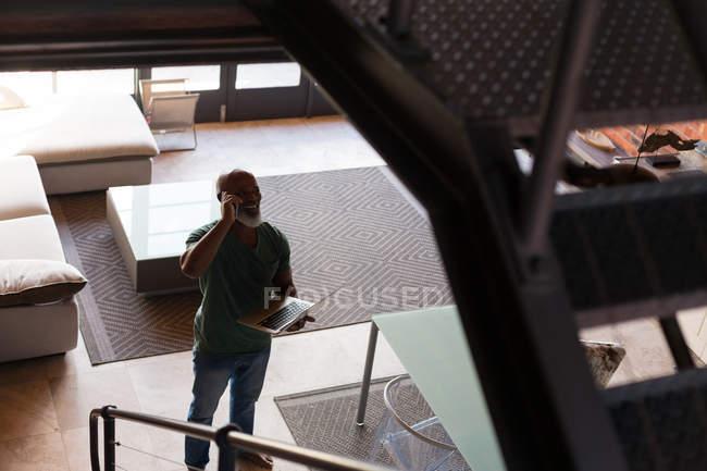Homme âgé parlant au téléphone tout en utilisant un ordinateur portable à la maison — Photo de stock
