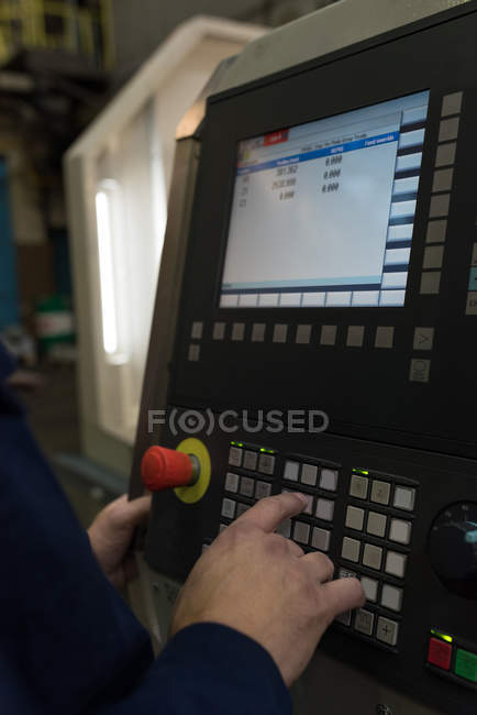 Mid section of technician operating machine in metal industry — Stock Photo