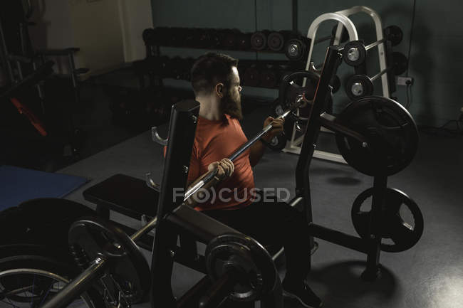 Handicapped man ready for lifting barbell in gym — стокове фото