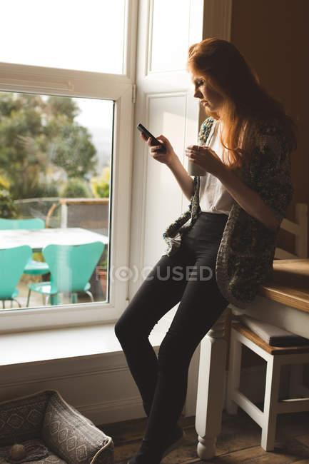 Женщина, имея кофе во время использования мобильного телефона — стоковое фото