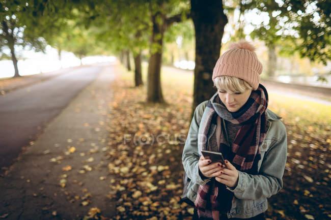 Молодая женщина в теплой одежде пользуется мобильным телефоном в парке — стоковое фото