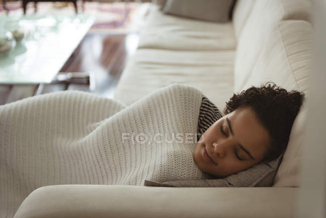 Woman wrapped in blanket sleeping on sofa at home — Stock Photo