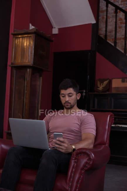 Чоловічий клієнтів за допомогою мобільного телефону і ноутбук в перукарні---16 — стокове фото