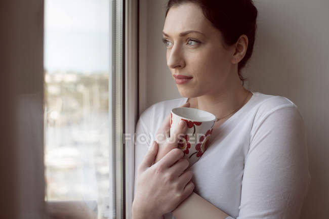 Thoughtful woman holding coffee mug and looking through window. — Stock Photo