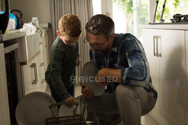 Отец и сын, Организация посуды на кухне дома — стоковое фото