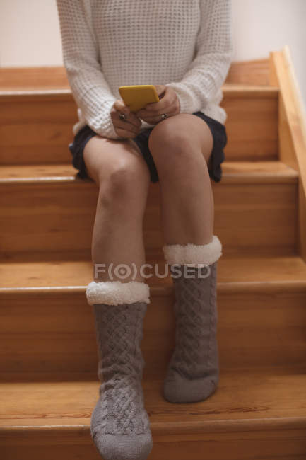 Woman using mobile phone on staircase at home — Stock Photo