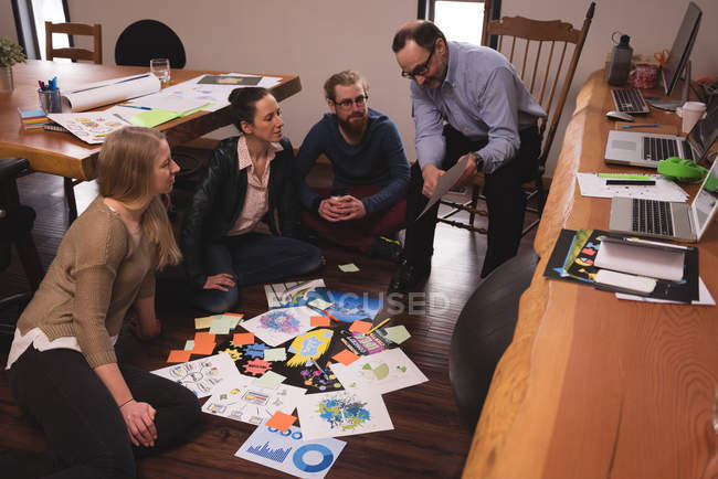 Business colleagues discussing over graph documents in office — Stock Photo