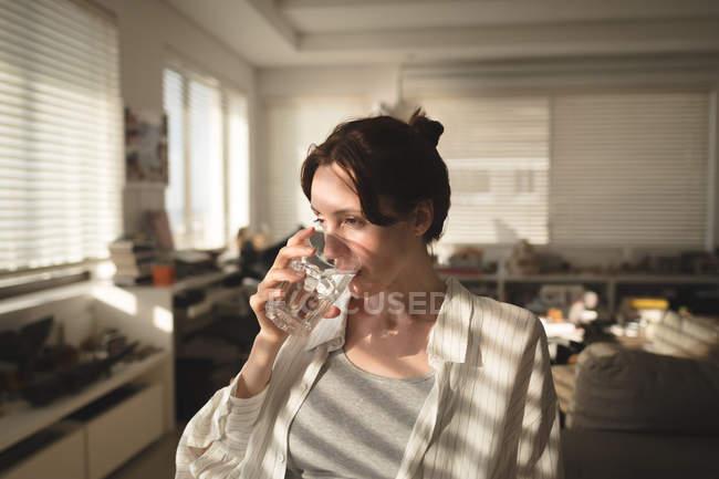 Mulher jovem, olhando para longe enquanto água potável na sala de estar em casa — Fotografia de Stock