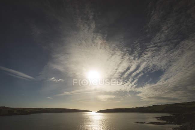 Belo pôr do sol e nuvens sobre o lago no campo — Fotografia de Stock