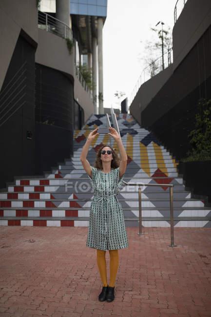 Mujer en gafas de sol tomando selfie con teléfono móvil en zona peatonal - foto de stock