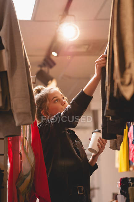 Beautiful girl selecting clothes from rack in shopping mall — Stock Photo