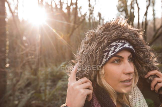 Молода жінка в балахон стояти під лісом. — стокове фото