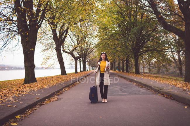 Geschäftsfrau mit Handy steht im Herbst auf der Straße — Stockfoto