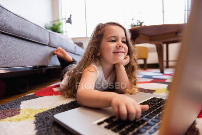 Girl лежачи на килимі і використовуючи ноутбук у вітальні на дому — стокове фото