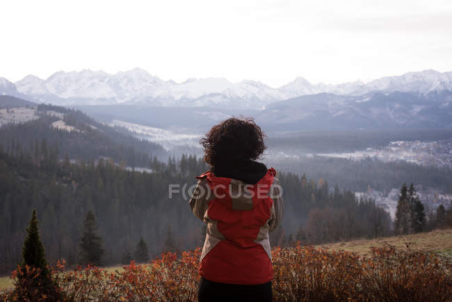 Rear view of woman in warm clothing standing near countryside — Stock Photo