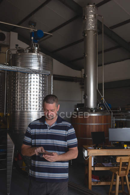Male worker using digital tablet in gin factory — Stock Photo