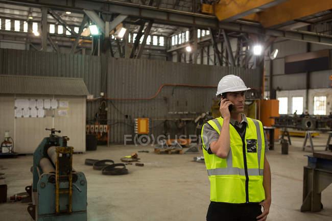 Marine engineer talking on mobile phone in workshop — Stock Photo