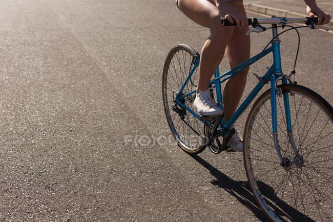 Нижняя часть женщины на велосипеде в солнечный день — стоковое фото