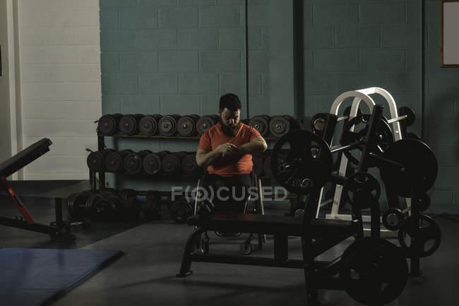 Недостатками человек, наблюдая за время на часы в тренажерном зале — стоковое фото
