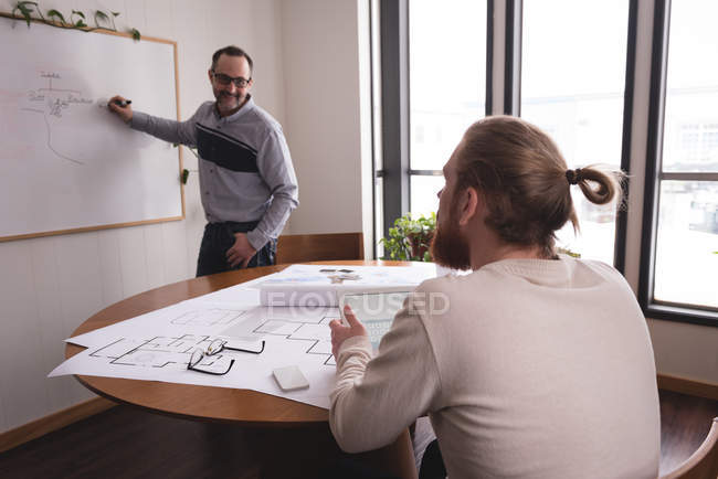 Male executive discussing chart on whiteboard with coworker in office — Stock Photo