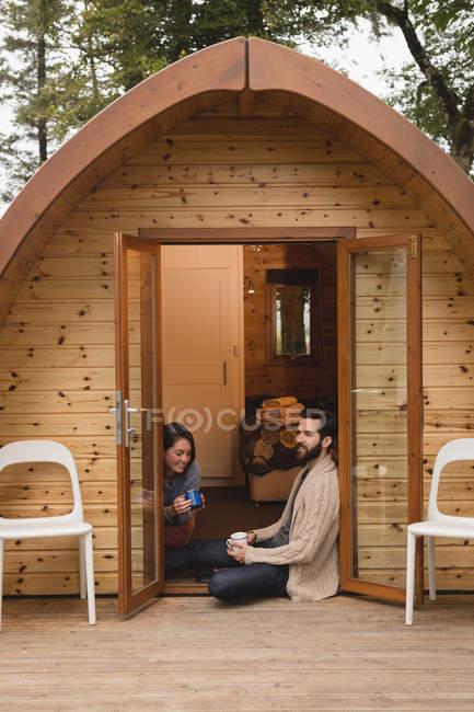 Счастливая пара, имея кофе вне кабины журнала — стоковое фото