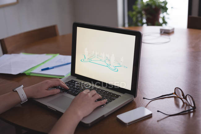 Cropped view of female executive using laptop at desk in office — Stock Photo
