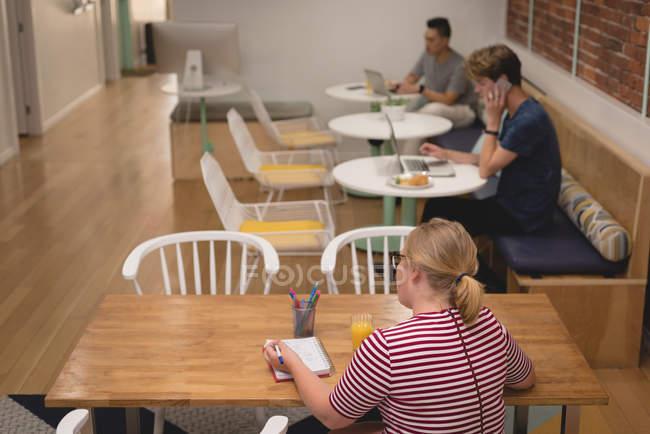 Жіночий виконавчий писати щоденник в офісі — стокове фото
