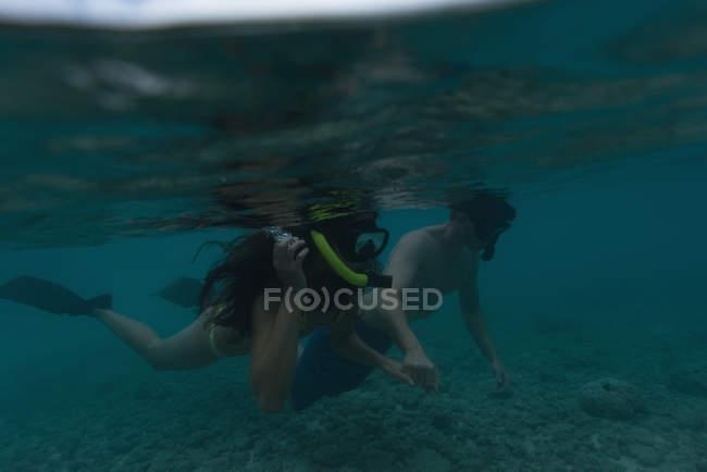 Пара, плавание под водой в бирюзовое море на скалистом дне — стоковое фото