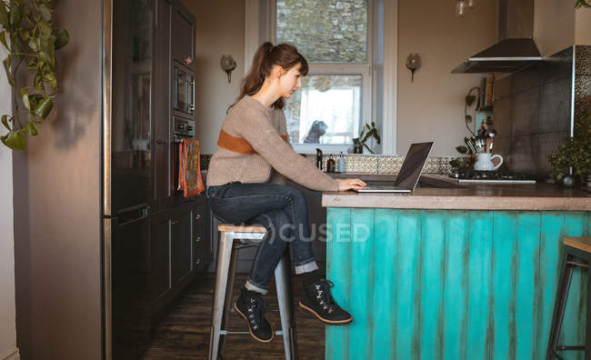 Woman using laptop in kitchen at home — Stock Photo